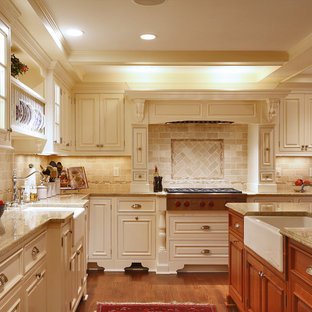 Large traditional eat-in kitchen ideas - Large elegant u-shaped medium tone wood floor eat-in kitchen photo in New York with a farmhouse sink, raised-panel cabinets, beige cabinets, granite countertops, beige backsplash, stainless steel appliances, an island and travertine backsplash