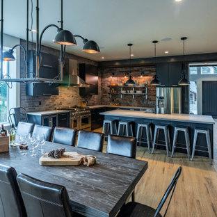 バンクーバーの大きいモダンスタイルのおしゃれなキッチン (アンダーカウンターシンク、フラットパネル扉のキャビネット、黒いキャビネット、クオーツストーンカウンター、赤いキッチンパネル、レンガのキッチンパネル、シルバーの調理設備の、クッションフロア、茶色い床、白いキッチンカウンター) の写真