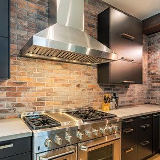 バンクーバーの広いモダンスタイルのおしゃれなキッチン (アンダーカウンターシンク、フラットパネル扉のキャビネット、黒いキャビネット、クオーツストーンカウンター、赤いキッチンパネル、レンガのキッチンパネル、シルバーの調理設備、クッションフロア、茶色い床、白いキッチンカウンター) の写真