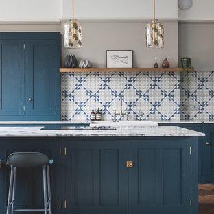 Exempel på ett stort modernt kök, med en rustik diskho, skåp i shakerstil, blå skåp, marmorbänkskiva, blått stänkskydd, stänkskydd i cementkakel, rostfria vitvaror, mörkt trägolv, en köksö och brunt golv