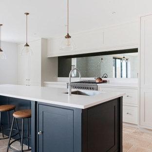エセックスの中くらいのトランジショナルスタイルのおしゃれなアイランドキッチン (ミラータイルのキッチンパネル、シルバーの調理設備、白いキッチンカウンター、シングルシンク、インセット扉のキャビネット、ベージュの床、トラバーチンの床、白いキャビネット) の写真