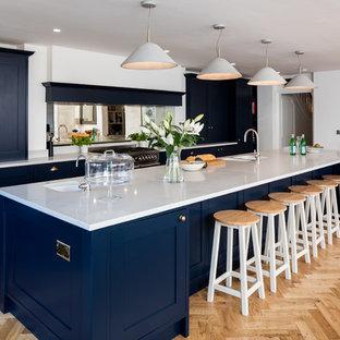 Einzeilige, Große Klassische Küche mit Doppelwaschbecken, Schrankfronten mit vertiefter Füllung, blauen Schränken, Rückwand aus Spiegelfliesen, hellem Holzboden, Kücheninsel und beigem Boden in Berkshire