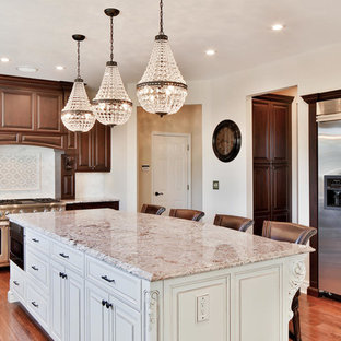 This is an example of a large traditional u-shaped eat-in kitchen in New York with an undermount sink, raised-panel cabinets, brown cabinets, granite benchtops, white splashback, stone tile splashback, stainless steel appliances, medium hardwood floors and with island.