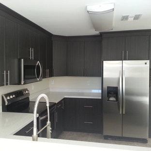フェニックスの広いおしゃれなキッチン (ドロップインシンク、フラットパネル扉のキャビネット、グレーのキャビネット、白いキッチンパネル、ガラスタイルのキッチンパネル、シルバーの調理設備、無垢フローリング、再生ガラスカウンター) の写真
