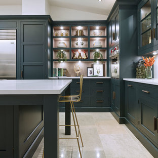 Mid-sized transitional l-shaped eat-in kitchen in London with a drop-in sink, shaker cabinets, green cabinets, quartzite benchtops, white splashback, stainless steel appliances, marble floors, with island, beige floor and white benchtop.