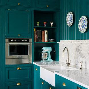 ロンドンの中くらいのトラディショナルスタイルのおしゃれなアイランドキッチン (エプロンフロントシンク、シェーカースタイル扉のキャビネット、黒いキャビネット、大理石カウンター、ベージュキッチンパネル、セラミックタイルのキッチンパネル、シルバーの調理設備、無垢フローリング、ベージュの床、白いキッチンカウンター) の写真