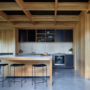 Photo of a midcentury kitchen in Melbourne with black cabinets, stainless steel benchtops, white splashback, ceramic splashback, black appliances, concrete floors, with island, grey floor, an integrated sink and flat-panel cabinets.