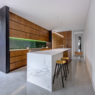 Photo of a contemporary l-shaped kitchen in Sydney with an undermount sink, flat-panel cabinets, medium wood cabinets, green splashback, stainless steel appliances, concrete floors, with island, grey floor and white benchtop.