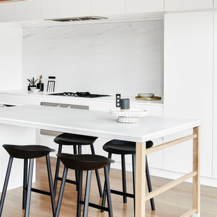 This is an example of a modern kitchen in Melbourne with flat-panel cabinets, white cabinets, white splashback, stainless steel appliances, light hardwood floors and with island.