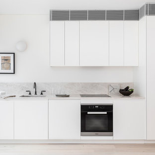 Design ideas for a modern single-wall kitchen in Sydney with an undermount sink, flat-panel cabinets, white cabinets, beige splashback, stainless steel appliances, light hardwood floors, beige floor and beige benchtop.
