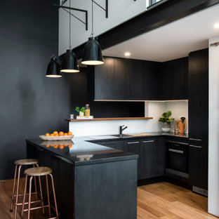 Design ideas for a contemporary u-shaped kitchen in Sydney with an undermount sink, flat-panel cabinets, black cabinets, white splashback, panelled appliances, medium hardwood floors, a peninsula, brown floor and black benchtop.