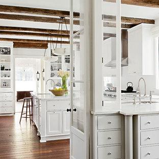 Cette image montre une cuisine chalet avec un placard à porte vitrée, des portes de placard blanches et une crédence blanche.