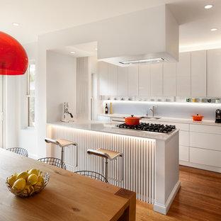 Zweizeilige, Kleine Moderne Wohnküche mit Unterbauwaschbecken, flächenbündigen Schrankfronten, weißen Schränken, Quarzwerkstein-Arbeitsplatte, Küchenrückwand in Blau, Glasrückwand, Elektrogeräten mit Frontblende, braunem Holzboden und Kücheninsel in Boston