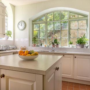 デヴォンの中サイズのヴィクトリアン調のおしゃれなキッチン (ドロップインシンク、落し込みパネル扉のキャビネット、白いキャビネット、テラコッタタイルの床) の写真