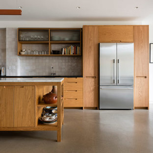 This is an example of a large contemporary l-shaped kitchen/diner in London with a single-bowl sink, flat-panel cabinets, medium wood cabinets, marble worktops, white splashback, mosaic tiled splashback, stainless steel appliances, concrete flooring, an island, grey floors and white worktops.