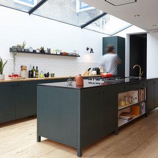 ロンドンの中くらいのコンテンポラリースタイルのおしゃれなキッチン (アンダーカウンターシンク、フラットパネル扉のキャビネット、緑のキャビネット、木材カウンター、白いキッチンパネル、サブウェイタイルのキッチンパネル、淡色無垢フローリング、ベージュの床、ベージュのキッチンカウンター) の写真
