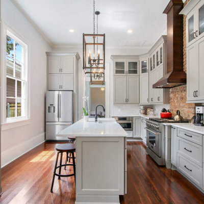 Mid-sized transitional l-shaped medium tone wood floor and brown floor enclosed kitchen photo in New Orleans with a farmhouse sink, recessed-panel cabinets, gray cabinets, quartzite countertops, white backsplash, marble backsplash, stainless steel appliances, an island and white countertops