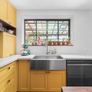 Inspiration pour une cuisine ouverte minimaliste en L de taille moyenne avec un évier de ferme, un placard à porte shaker, des portes de placard jaunes, un plan de travail en quartz modifié, une crédence blanche, une crédence en carreau de céramique, un électroménager en acier inoxydable, un sol en bois foncé, un îlot central, un sol marron, un plan de travail beige et un plafond en papier peint.