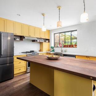 Exemple d'une cuisine ouverte moderne en L de taille moyenne avec un évier de ferme, un placard à porte shaker, des portes de placard jaunes, un plan de travail en quartz modifié, une crédence blanche, une crédence en carreau de céramique, un électroménager en acier inoxydable, un sol en bois foncé, un îlot central, un sol marron, un plan de travail beige et un plafond en papier peint.