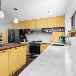Cette image montre une cuisine ouverte minimaliste en L de taille moyenne avec un évier de ferme, un placard à porte shaker, des portes de placard jaunes, un plan de travail en quartz modifié, une crédence blanche, une crédence en carreau de céramique, un électroménager en acier inoxydable, un sol en bois foncé, un îlot central, un sol marron, un plan de travail beige et un plafond en papier peint.
