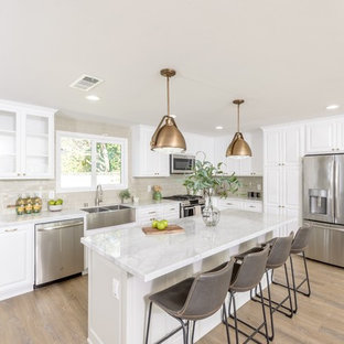 Mid-sized country l-shaped kitchen in Orange County with a farmhouse sink, raised-panel cabinets, white cabinets, marble benchtops, metallic splashback, ceramic splashback, stainless steel appliances, with island, beige floor and orange benchtop.