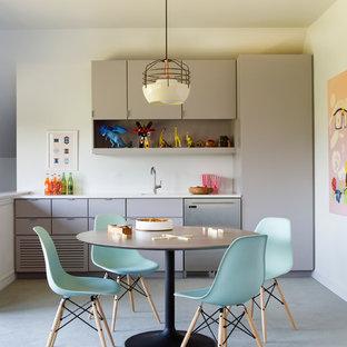 Cette photo montre une grand cuisine tendance avec un placard à porte plane, des portes de placard beiges, un électroménager en acier inoxydable et moquette.