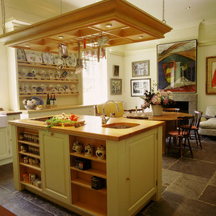 Photo of a large traditional galley kitchen/diner in London with wood worktops, a belfast sink, raised-panel cabinets, slate flooring, an island, grey floors and white worktops.