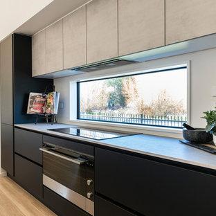 Idéer för ett mellanstort modernt kök, med en nedsänkt diskho, släta luckor, svarta skåp, laminatbänkskiva, vitt stänkskydd, fönster som stänkskydd, rostfria vitvaror, laminatgolv, en köksö och brunt golv