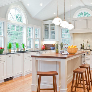 Elegant kitchen photo in Boston with beaded inset cabinets, wood countertops, white cabinets, white backsplash and subway tile backsplash