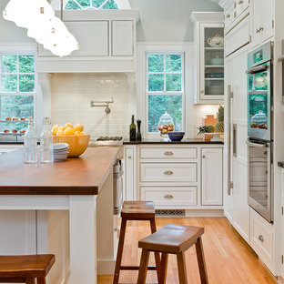 Kitchen - traditional kitchen idea in Boston with beaded inset cabinets, paneled appliances, subway tile backsplash, wood countertops and white cabinets