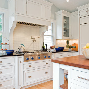 Traditional kitchen photos - Example of a classic kitchen design in Boston with beaded inset cabinets, subway tile backsplash, wood countertops, white cabinets, white backsplash and paneled appliances