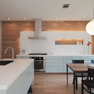 Contemporary eat-in kitchen remodeling - Eat-in kitchen - contemporary eat-in kitchen idea in Austin with stainless steel appliances, flat-panel cabinets, blue cabinets, quartz countertops, white backsplash and stone slab backsplash
