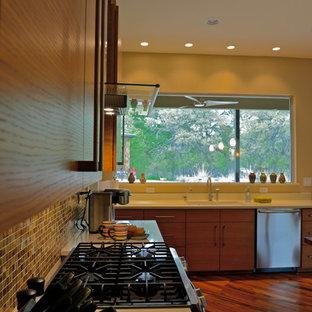 オースティンの大きいトランジショナルスタイルのおしゃれなキッチン (ドロップインシンク、フラットパネル扉のキャビネット、淡色木目調キャビネット、珪岩カウンター、マルチカラーのキッチンパネル、ガラスタイルのキッチンパネル、シルバーの調理設備、竹フローリング) の写真
