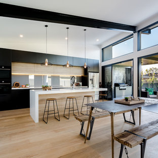 Design ideas for a large contemporary galley eat-in kitchen in Adelaide with flat-panel cabinets, glass sheet splashback, light hardwood floors, multiple islands, an undermount sink, black cabinets, grey splashback, beige floor and white benchtop.