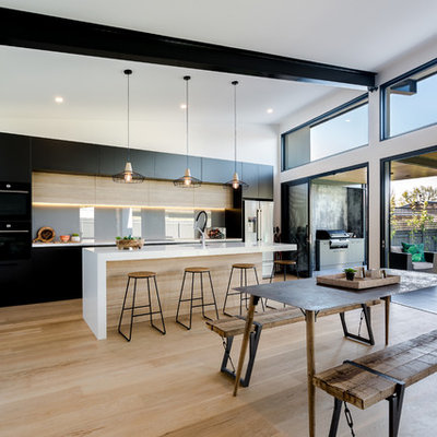 Example of a large trendy galley light wood floor and beige floor eat-in kitchen design in Adelaide with flat-panel cabinets, glass sheet backsplash, two islands, an undermount sink, black cabinets, gray backsplash and white countertops