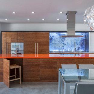 Imagen de cocina comedor de galera, contemporánea, con fregadero bajoencimera, armarios con paneles lisos, puertas de armario de madera oscura, electrodomésticos con paneles, suelo de cemento, una isla, suelo gris y encimeras naranjas