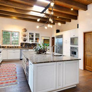 アルバカーキの広いサンタフェスタイルのおしゃれなキッチン (アンダーカウンターシンク、シェーカースタイル扉のキャビネット、白いキャビネット、御影石カウンター、マルチカラーのキッチンパネル、モザイクタイルのキッチンパネル、シルバーの調理設備、濃色無垢フローリング) の写真