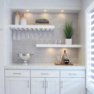 Idéer för ett stort modernt linjärt kök med öppen planlösning, med skåp i shakerstil, vita skåp, bänkskiva i kvarts, grått stänkskydd, stänkskydd i porslinskakel, rostfria vitvaror och en köksö