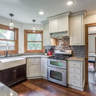 他の地域の中サイズのヴィクトリアン調のおしゃれなキッチン (エプロンフロントシンク、シェーカースタイル扉のキャビネット、グレーのキッチンパネル、ガラスタイルのキッチンパネル、シルバーの調理設備の、アイランドなし、グレーのキャビネット、クオーツストーンカウンター、無垢フローリング) の写真