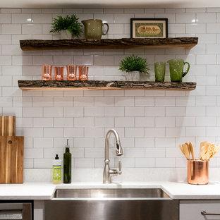 ワシントンD.C.の小さいエクレクティックスタイルのおしゃれなL型キッチン (エプロンフロントシンク、シェーカースタイル扉のキャビネット、白いキャビネット、クオーツストーンカウンター、白いキッチンパネル、サブウェイタイルのキッチンパネル、シルバーの調理設備の、アイランドなし、茶色い床、白いキッチンカウンター、クッションフロア) の写真