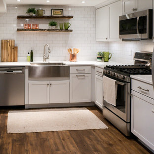 Small eclectic l-shaped kitchen in DC Metro with a farmhouse sink, shaker cabinets, white cabinets, quartz benchtops, white splashback, subway tile splashback, stainless steel appliances, no island, brown floor, white benchtop and vinyl floors.