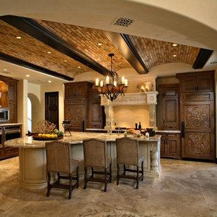 フェニックスの巨大な地中海スタイルのおしゃれなキッチン (レイズドパネル扉のキャビネット、濃色木目調キャビネット、御影石カウンター、パネルと同色の調理設備、トラバーチンの床、アンダーカウンターシンク、ベージュキッチンパネル、ライムストーンの床、ベージュの床、ベージュのキッチンカウンター) の写真