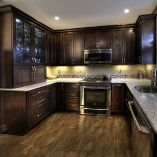 This is an example of a mid-sized traditional u-shaped separate kitchen in DC Metro with glass tile splashback, stainless steel appliances, an undermount sink, granite benchtops, recessed-panel cabinets, dark wood cabinets, multi-coloured splashback, ceramic floors and no island.