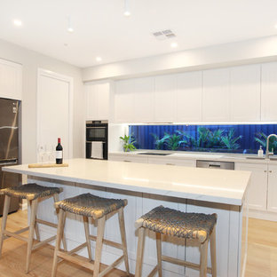Mid-sized modern u-shaped kitchen in Sunshine Coast with a drop-in sink, shaker cabinets, white cabinets, quartz benchtops, window splashback, stainless steel appliances, vinyl floors, yellow floor, white benchtop and with island.