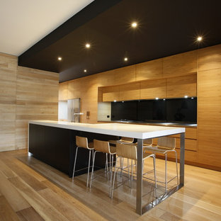 Mid-sized trendy galley medium tone wood floor eat-in kitchen photo in Melbourne with flat-panel cabinets, medium tone wood cabinets, black backsplash, glass sheet backsplash, stainless steel appliances and quartz countertops