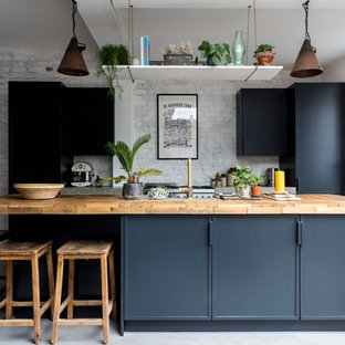 Design ideas for a mid-sized industrial single-wall kitchen in London with flat-panel cabinets, blue cabinets, wood benchtops, concrete floors, with island, grey floor and beige benchtop.