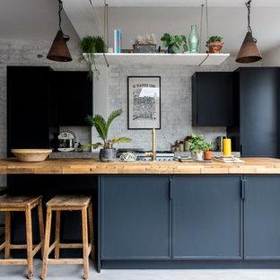 Einzeilige, Mittelgroße Industrial Küche mit flächenbündigen Schrankfronten, blauen Schränken, Arbeitsplatte aus Holz, Betonboden, Kücheninsel, grauem Boden und beiger Arbeitsplatte in London