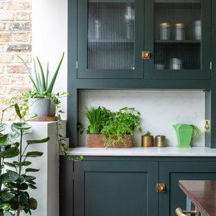 ロンドンの中サイズのエクレクティックスタイルのおしゃれなキッチン (エプロンフロントシンク、シェーカースタイル扉のキャビネット、緑のキャビネット、珪岩カウンター、メタリックのキッチンパネル、大理石の床、黒い調理設備、無垢フローリング、茶色い床、白いキッチンカウンター) の写真