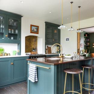 Inspiration för ett mellanstort vintage vit linjärt vitt kök och matrum, med skåp i shakerstil, gröna skåp, mellanmörkt trägolv, en köksö, brunt golv, en rustik diskho, bänkskiva i kvartsit, stänkskydd med metallisk yta, stänkskydd i marmor och svarta vitvaror