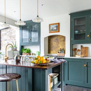 ロンドンの中サイズのエクレクティックスタイルのおしゃれなキッチン (エプロンフロントシンク、シェーカースタイル扉のキャビネット、緑のキャビネット、珪岩カウンター、メタリックのキッチンパネル、大理石の床、黒い調理設備、濃色無垢フローリング、茶色い床、白いキッチンカウンター) の写真